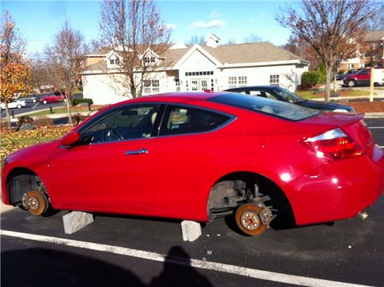 Red Car with Wheels and Tires Stolen